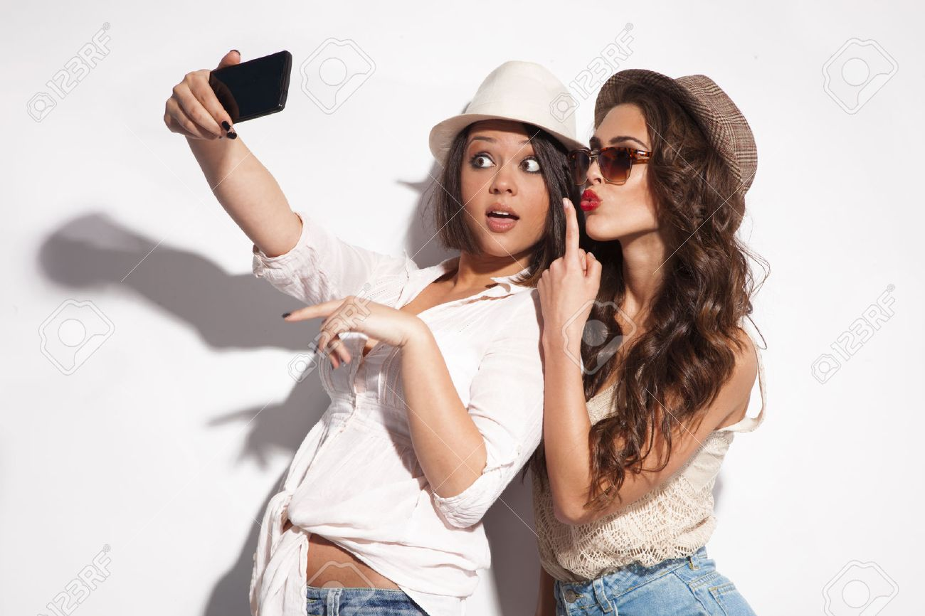 two young women taking selfie with mobile phone Standard-Bild - 28343887