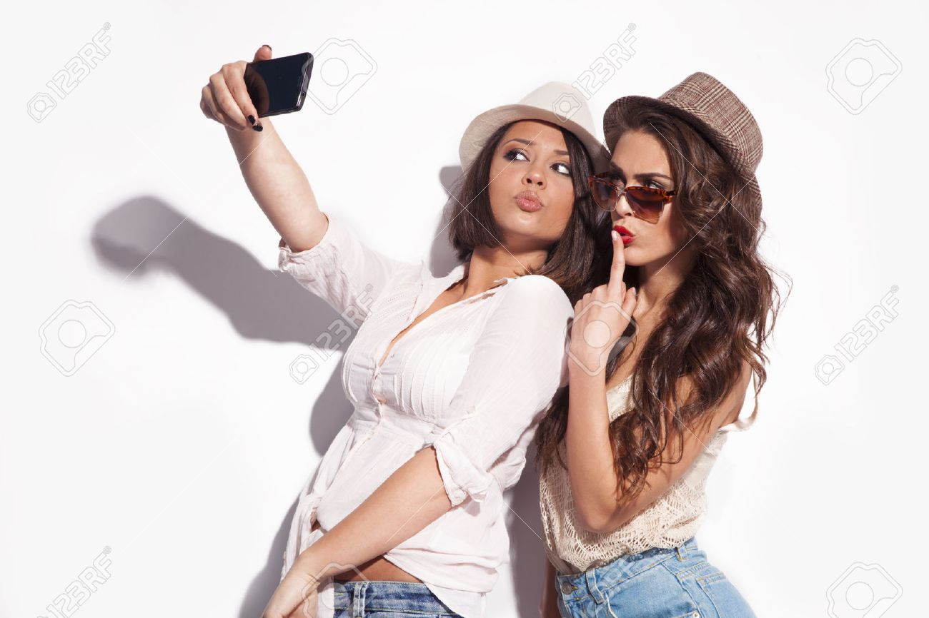 two young women taking selfie with mobile phone Standard-Bild - 28343900