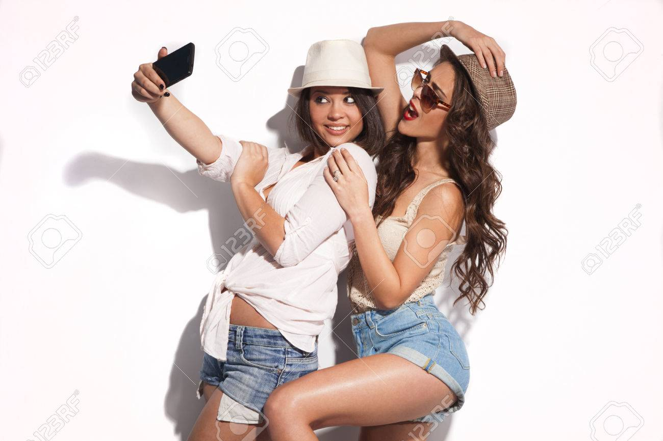 two young women taking selfie with mobile phone Standard-Bild - 28343901