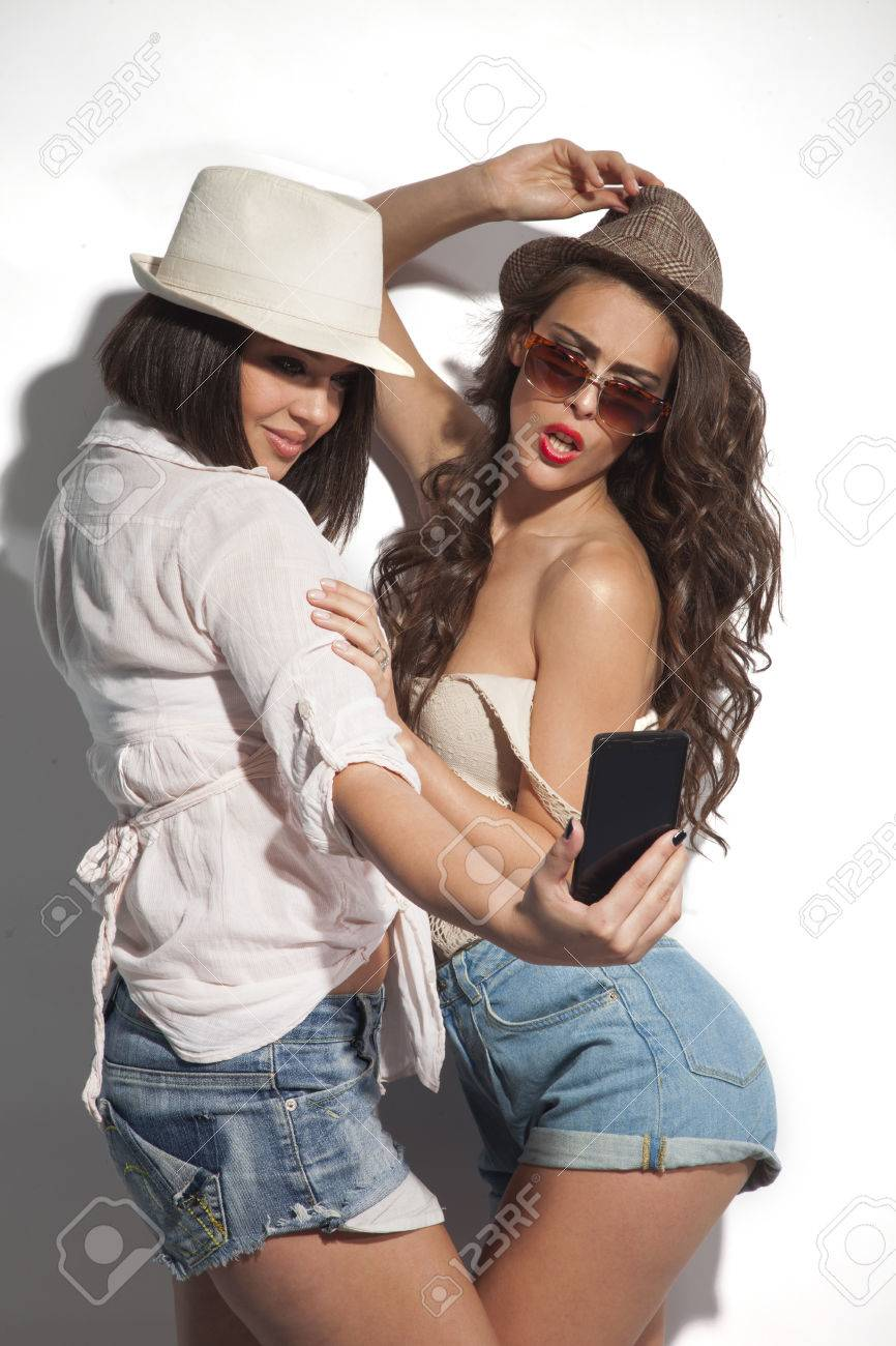 two young women taking selfie with mobile phone Standard-Bild - 28343905