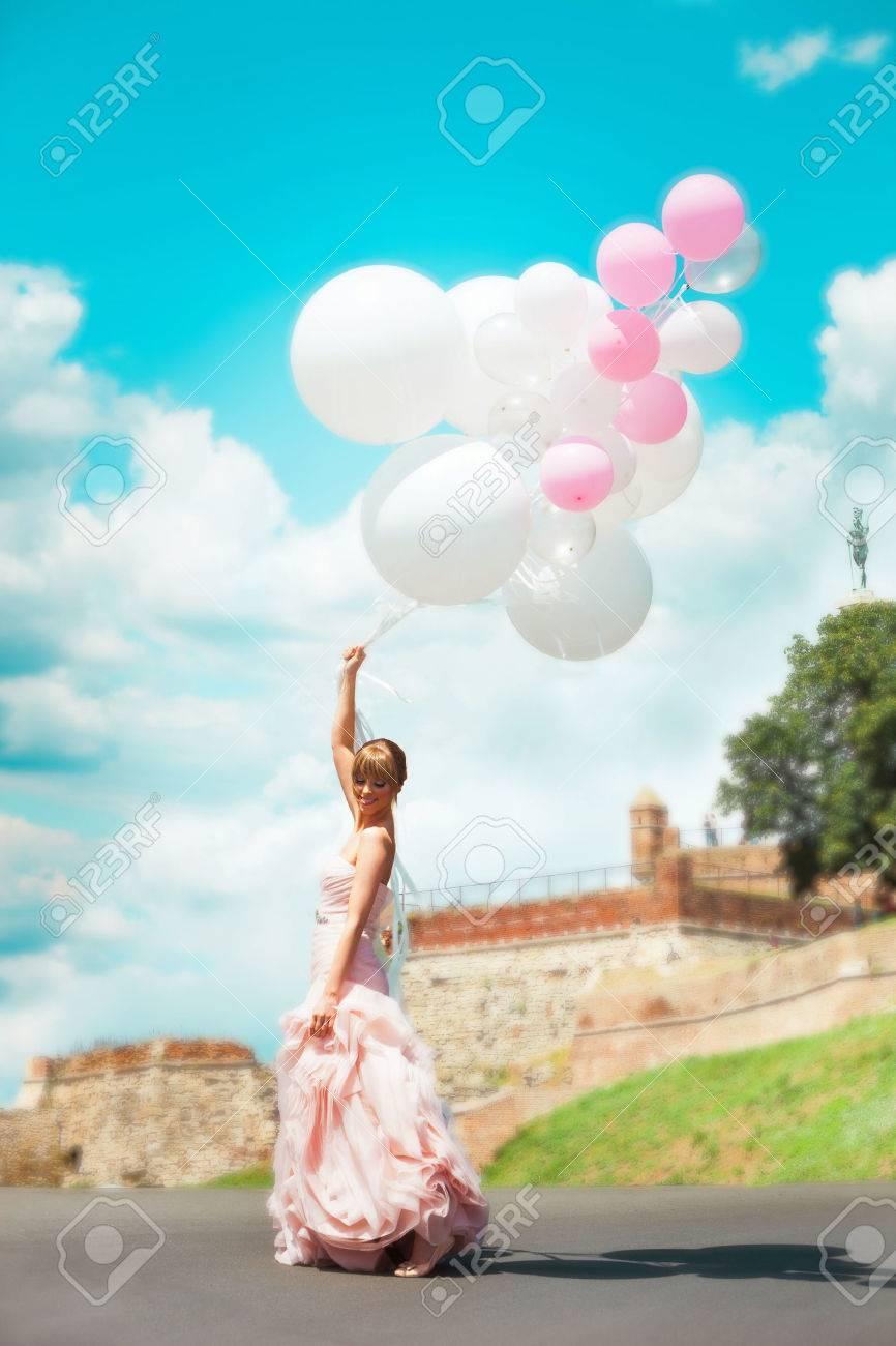 glückliche Braut im eleganten Hochzeitskleid halten Luftballons im Freien im Sommer Tag, Ganzkörperfoto, Belgrad Festung im Hintergrund Standard-Bild - 29673936