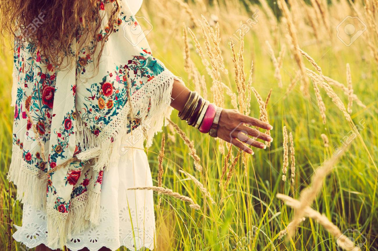 woman wearing boho style clothes touching grass, hand with lot of braceletes, summer day in the field, retro colors Standard-Bild - 30148348