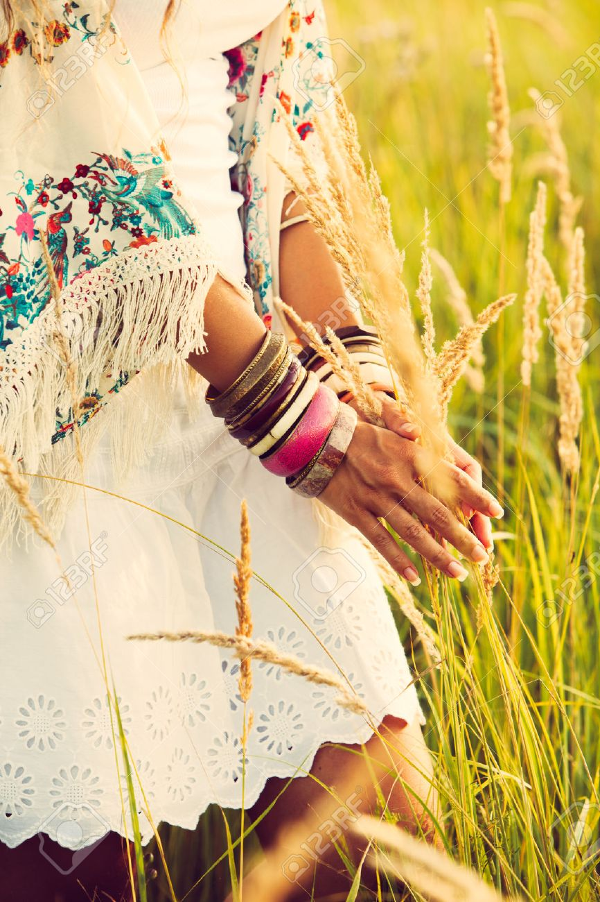 woman wearing boho style clothes touching grass, hand with lot of braceletes, summer day in the field, retro colors Standard-Bild - 30148350