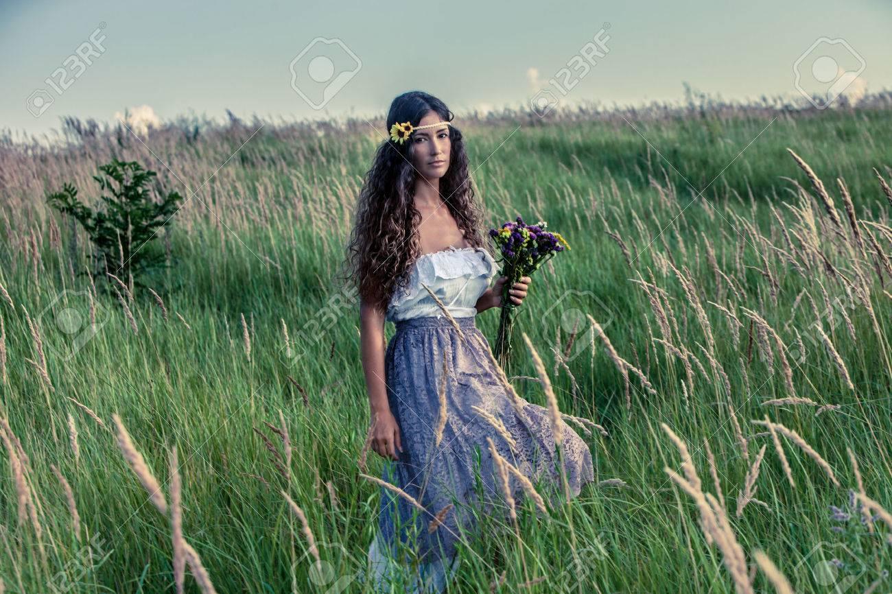 mujer joven en ropa de estilo boho caminar con el ramo de flores en la mano