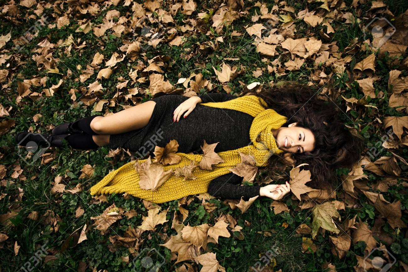 Banque d images - Sourire beau mensonge de femme dans l herbe et les  feuilles d automne en costume vert foncé et à long foulard de laine jaune 0c9475be6e6