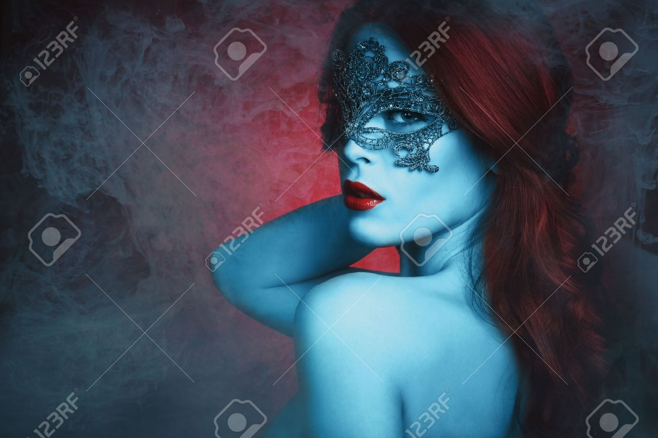 fantasy  beautiful young woman with lace mask, blue skin and red hair in haze Standard-Bild - 36859508