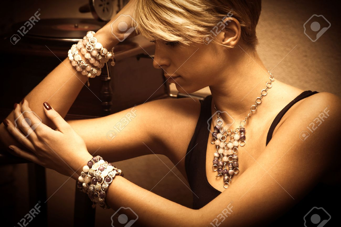 short hair blond elegant young woman portrait wearing jewelry, necklace and lot of bracelets, indoor shot, side view Standard-Bild - 38272230