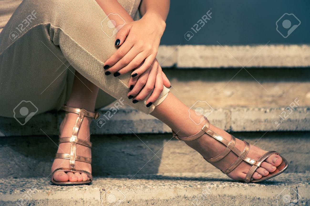 woman legs in high heel golden sandals and pants sit on stairs, outdoor shot, close up Standard-Bild - 39504360