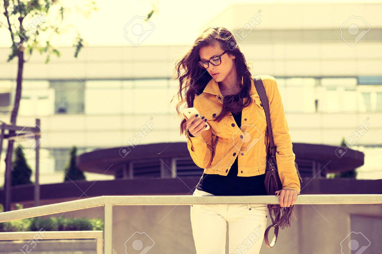 young urban woman with eyeglasses using smartphone,  outdoor shot in the city, retro colors Standard-Bild - 39824610