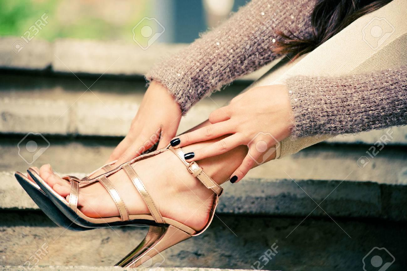 woman legs in high heel golden sandals lean on stairs, outdoor shot, close up Standard-Bild - 40256884