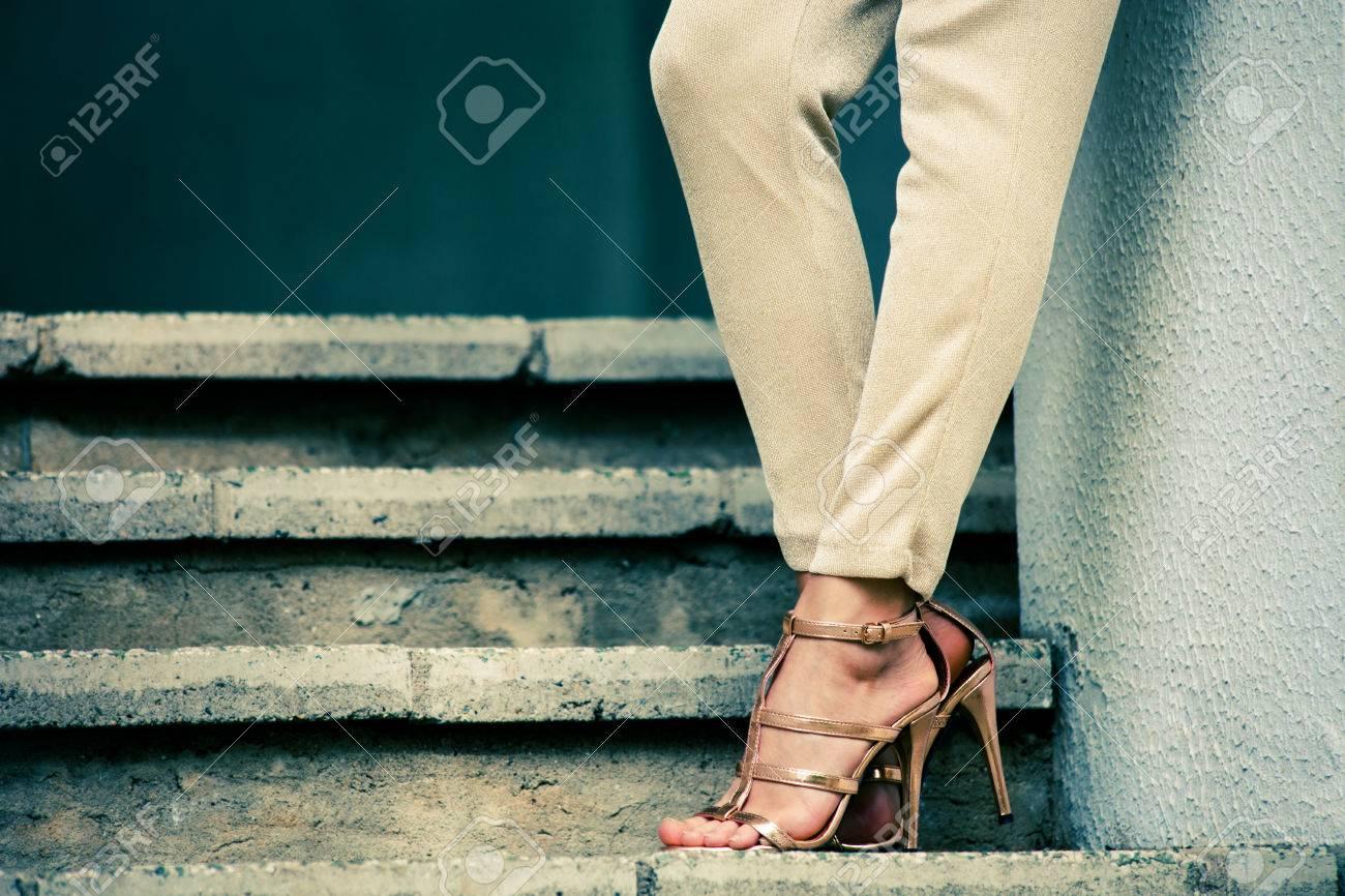 Piernas de la mujer en tacón alto sandalias doradas de pie en las escaleras, tiro al aire libre
