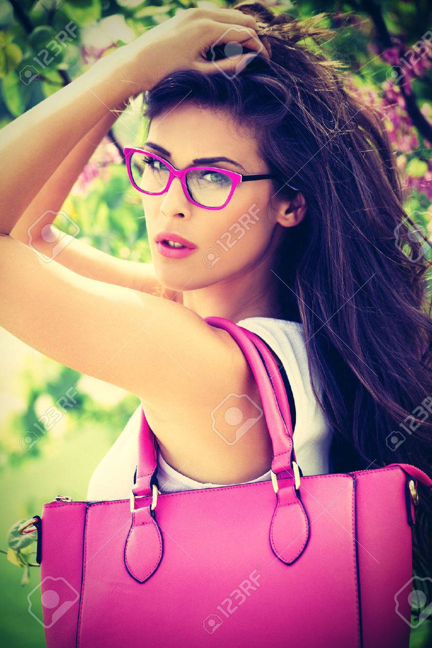 city young woman with pink fashion accessories. bag and eyeglasses, outdoor in park Standard-Bild - 41160358