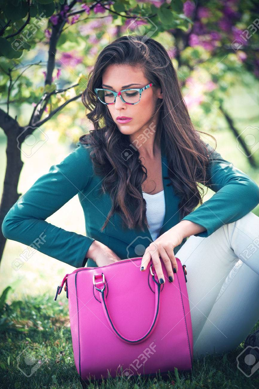 city young woman with fashion accessories. bag and eyeglasses, outdoor in park Standard-Bild - 41160360