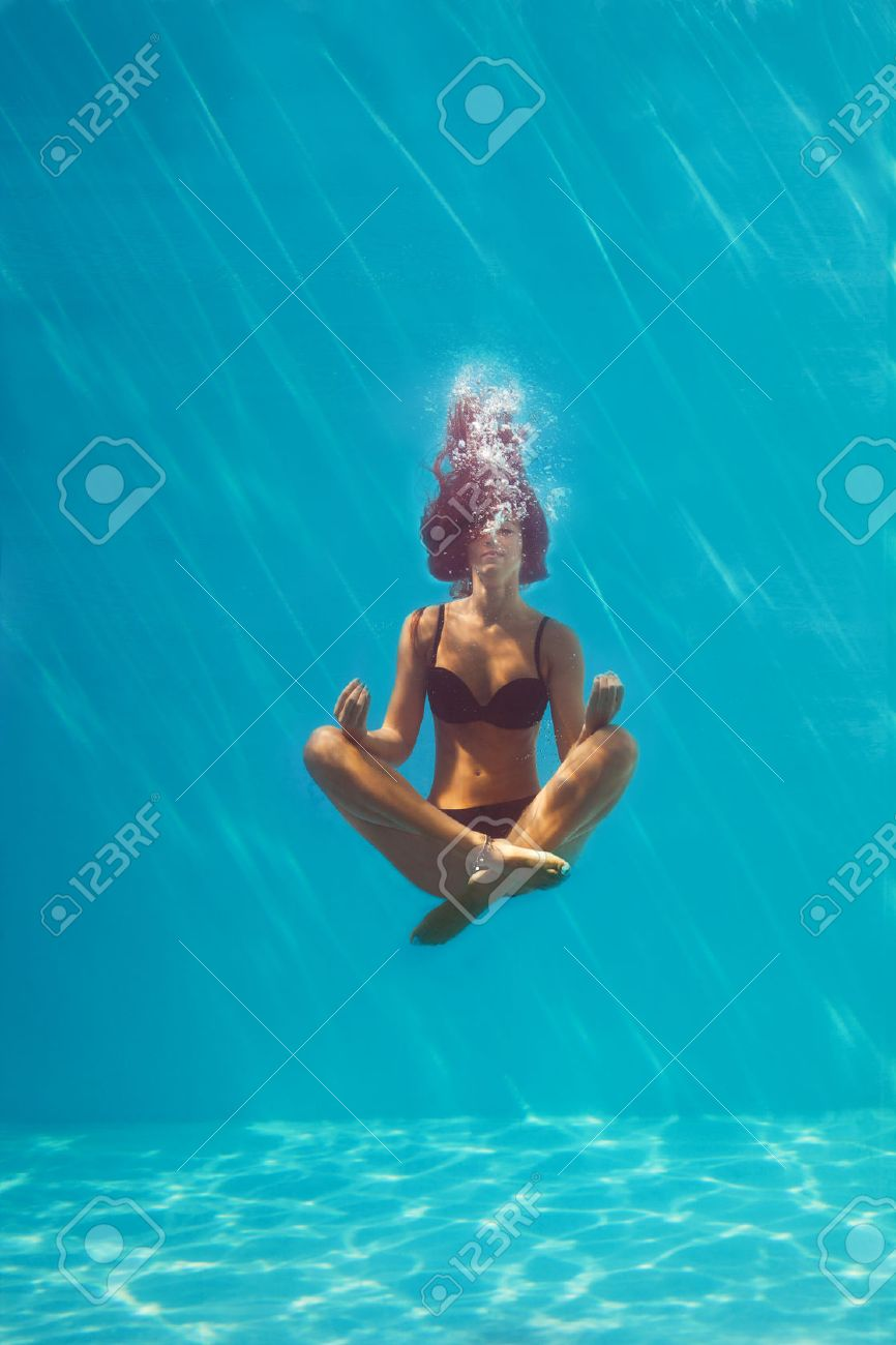 young woman in black bikini in yoga position underwater in diving aquarium, full body shot, front view through the glass Standard-Bild - 44395504