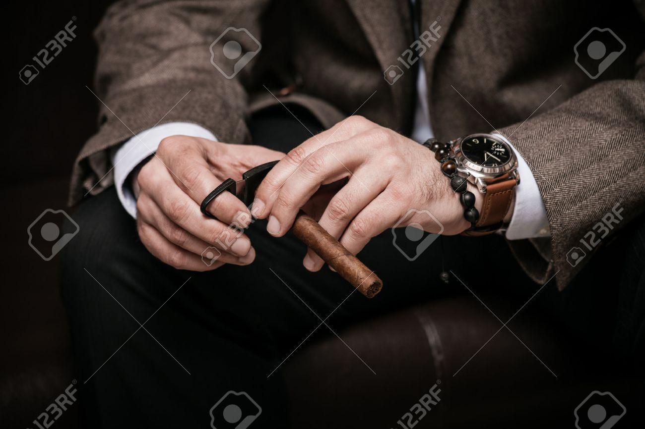 elegant man wearing suit and white shirt cut Cuban cigar indoor shot, closeup, selective focus Standard-Bild - 46646144