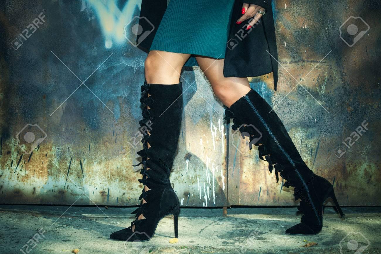 taille 40 02d9e cd8d3 Jambes de femme en bottes noires à talons hauts et jupe courte tir  extérieur contre porte en métal vieille