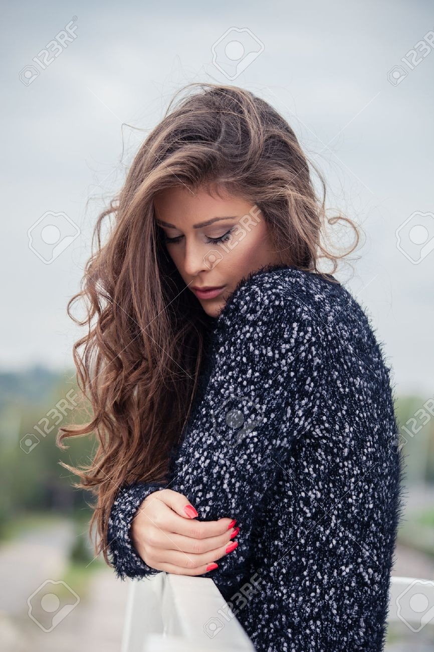 pensive beautiful young long hair woman in cardigan, outdoor autumn day portrait Standard-Bild - 47346562