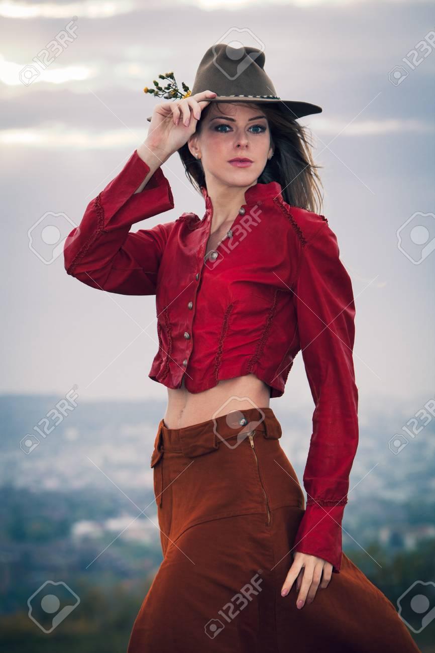 f1a1b342f Joven rubia de moda con el sombrero en la parte superior de la colina con  falda larga marrón y chaqueta de cuero roja
