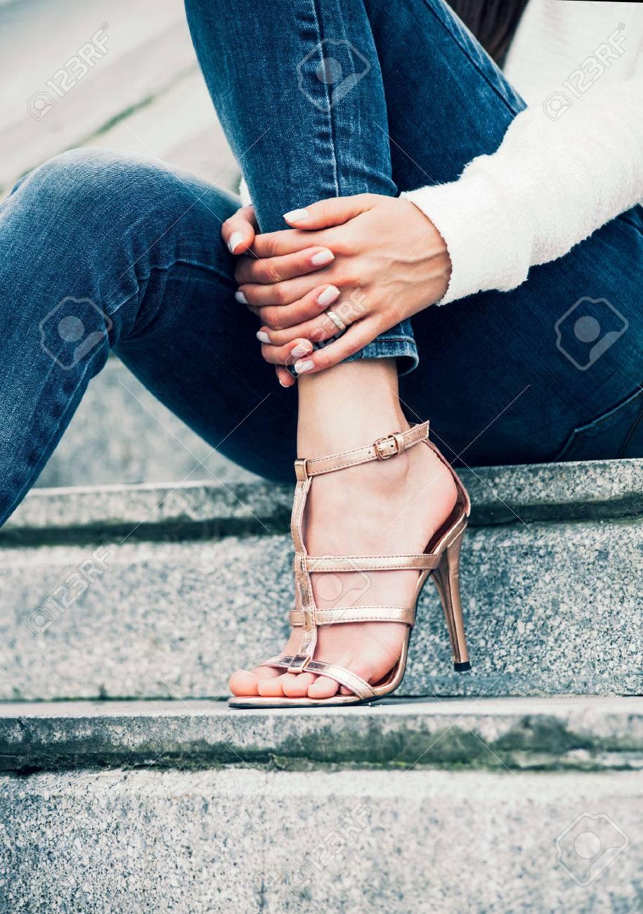 Mujer joven en los zapatos de tacón alto y pantalones vaqueros azules en tiro al aire libre escaleras