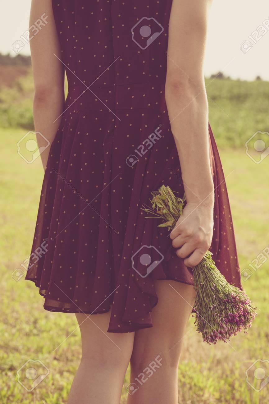 Mujer joven en vestido rojo y un ramo de flores silvestres de nuevo foto inferior del cuerpo