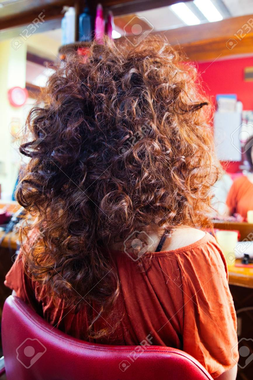 Woman With Long Curly Hair At Hairdresser Back View Closeup Stock