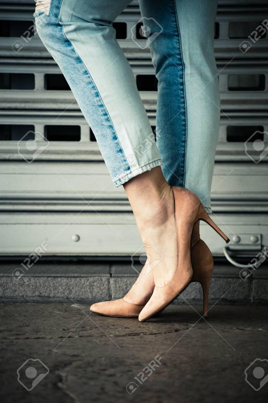 Piernas de mujer en zapatos de tacón alto y tejanos al aire libre en la ciudad