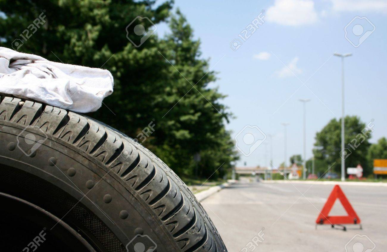 Car tire and a red triangle on the road Stock Photo - 1950789