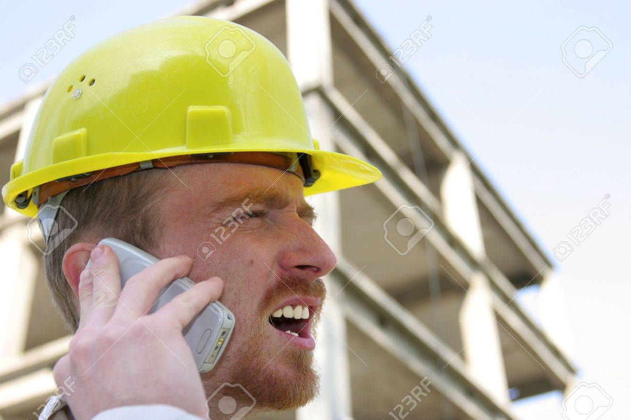 Man with helmet talking on a cell phone in front of a building construction Stock Photo - 1950624