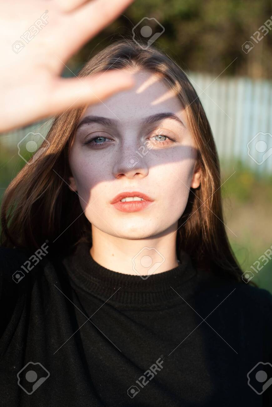 A Young Girl Covers Her Face With Her Hand. The Sun's Rays Fall.. Stock  Photo, Picture And Royalty Free Image. Image 128952168.
