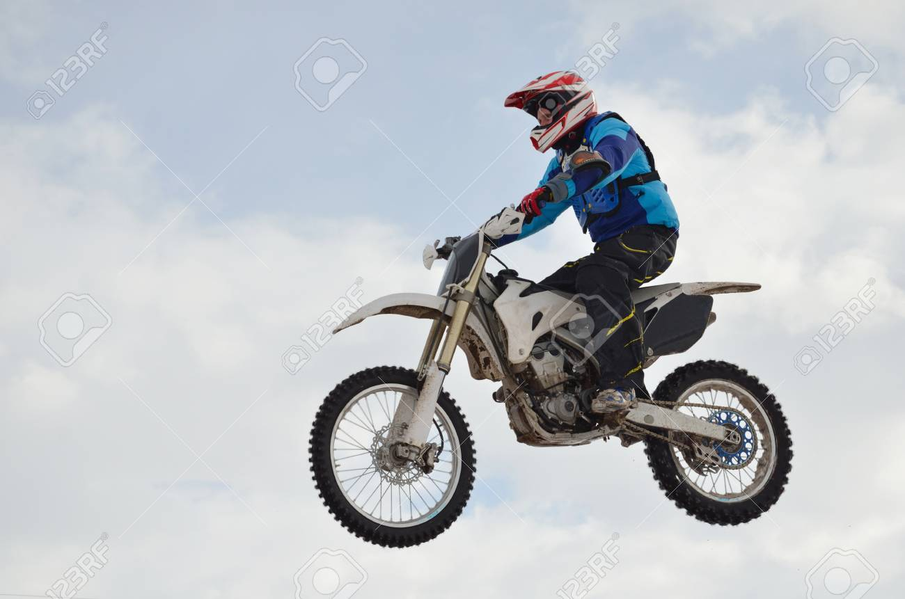 motocross rider performs jump, located high in the air against the blue sky Stock Photo - 9138598