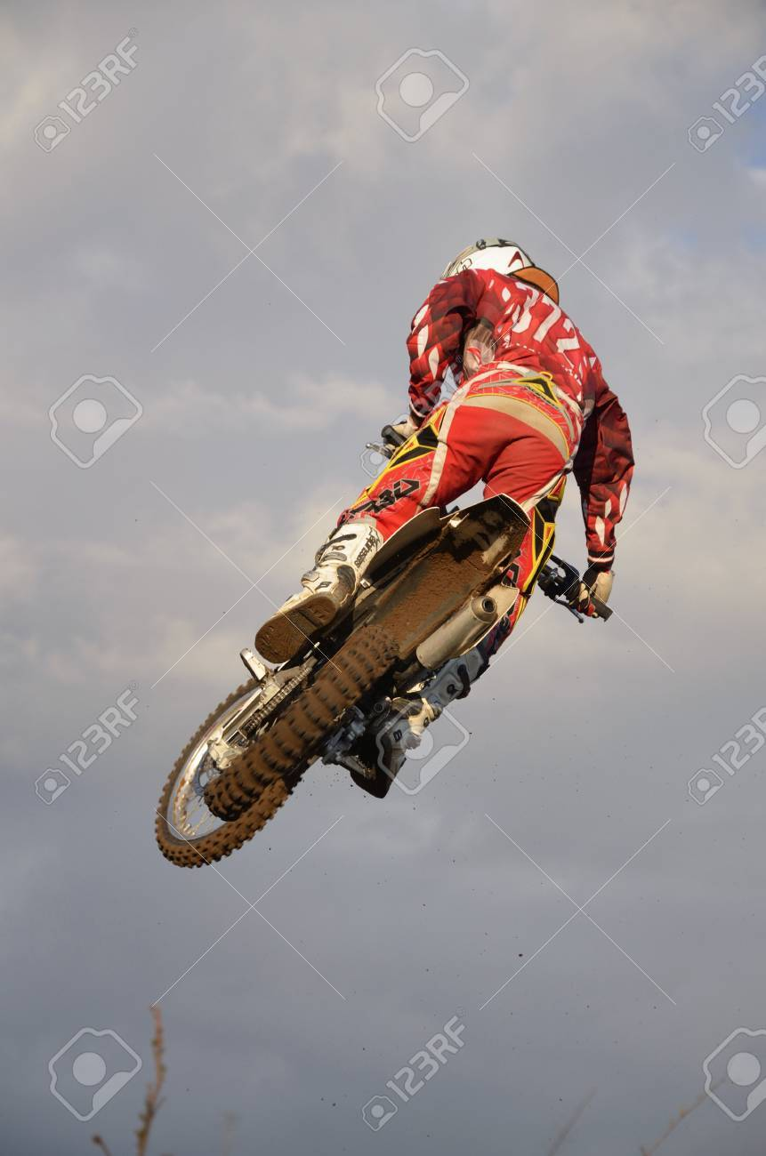 RUSSIA, SAMARA, CHAPAYEVSK - OCTOBER 17: The spectacular jump motocross racer I. Baranov on the background the Open Cup