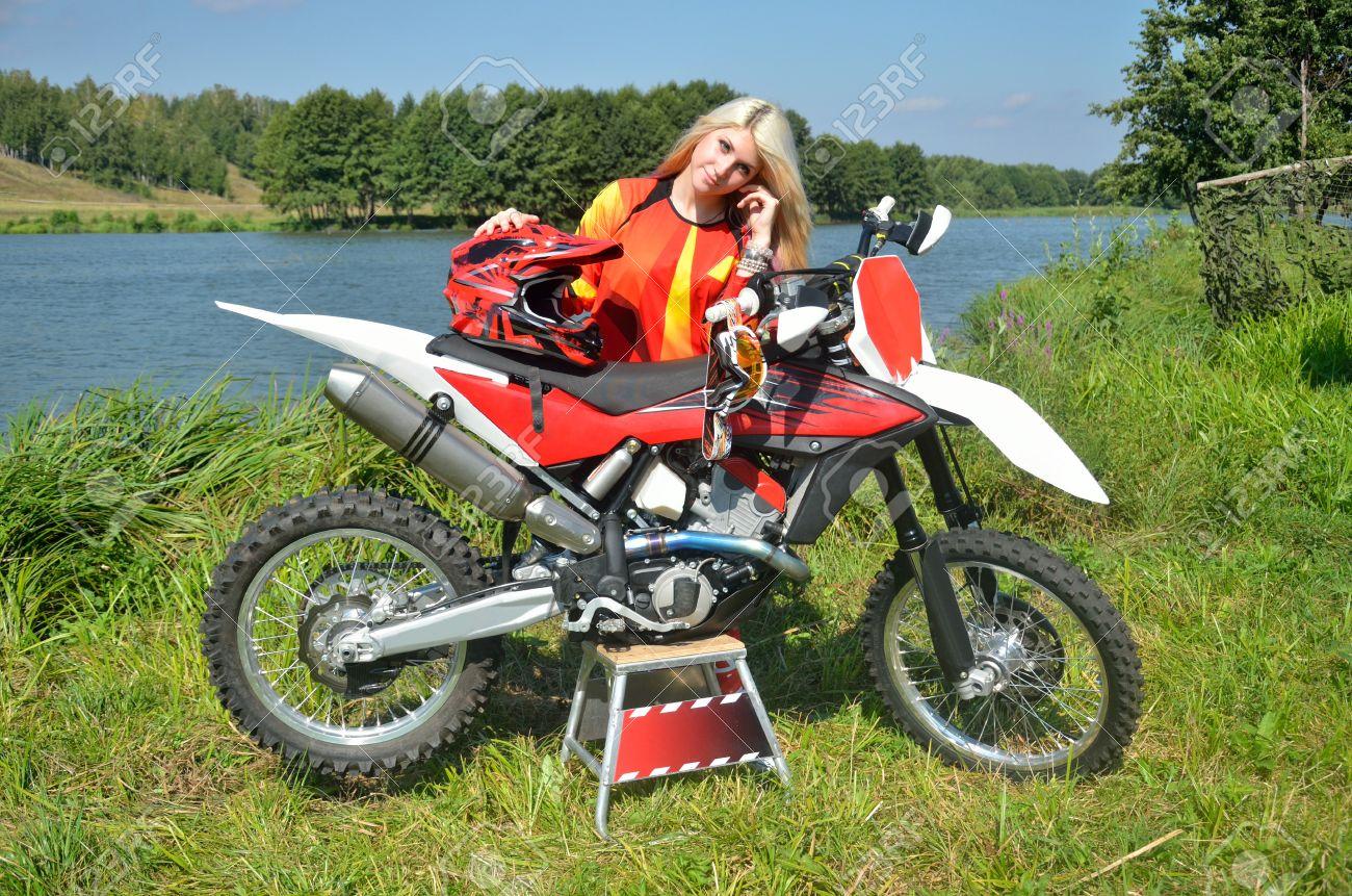 Immagini Stock - Ragazza Con I Capelli Biondi è In Piedi, Appoggiato Al Moto  Per Motocross, Mise Una Mano Su Un Casco. Image 15201412.