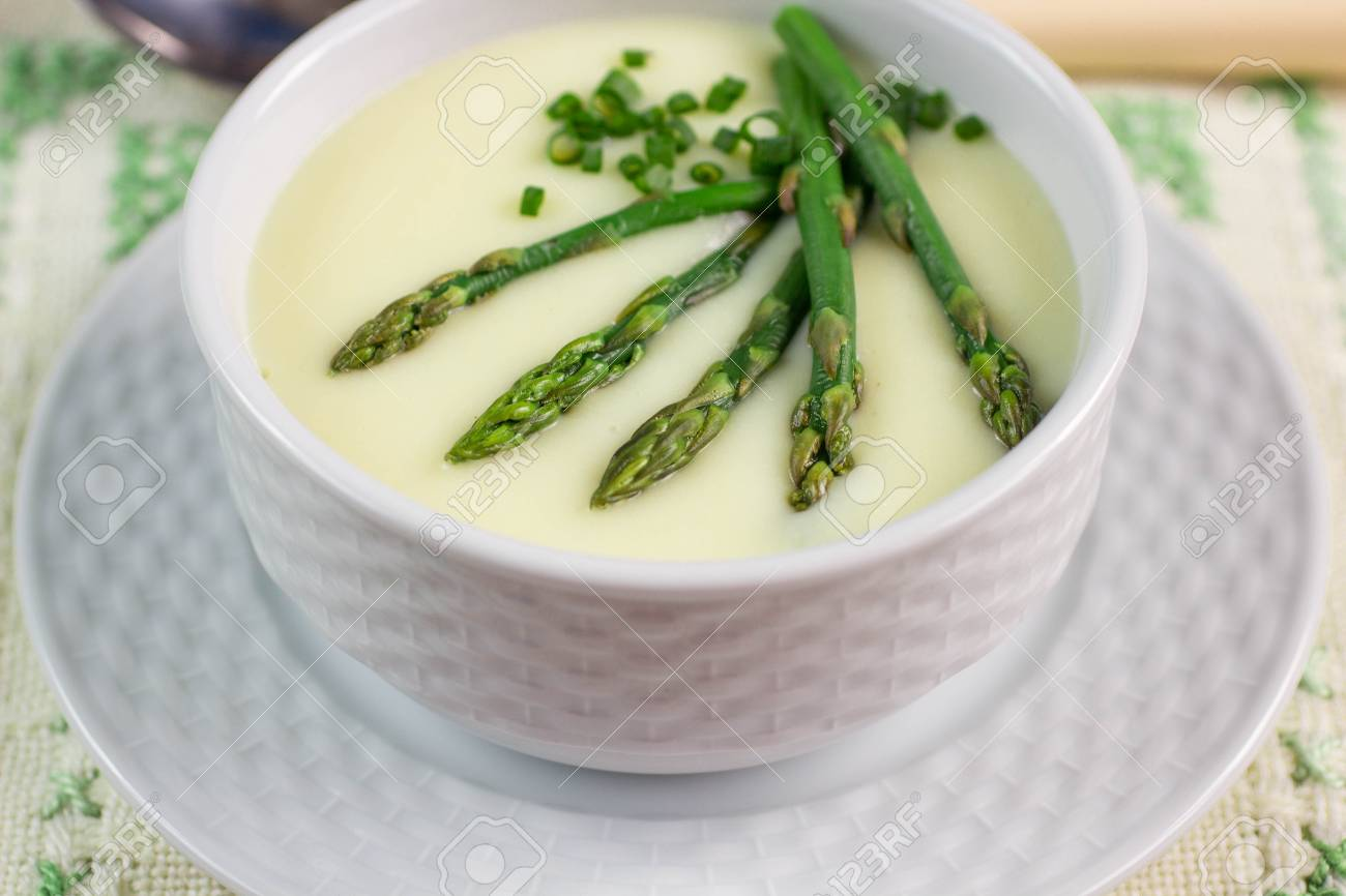 A delicious soup puree of asparagus in a white plate. The rustic style.  Selective 3e2d91311cc9