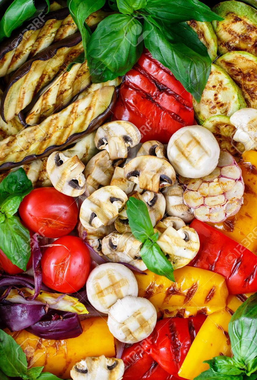 Grilled fresh vegetables - red and yellow bell peppers, purple onions, tomatoes, garlic, eggplants, zucchini and mushrooms champignons. Served with Basil. Selective focus, top view - 145974911