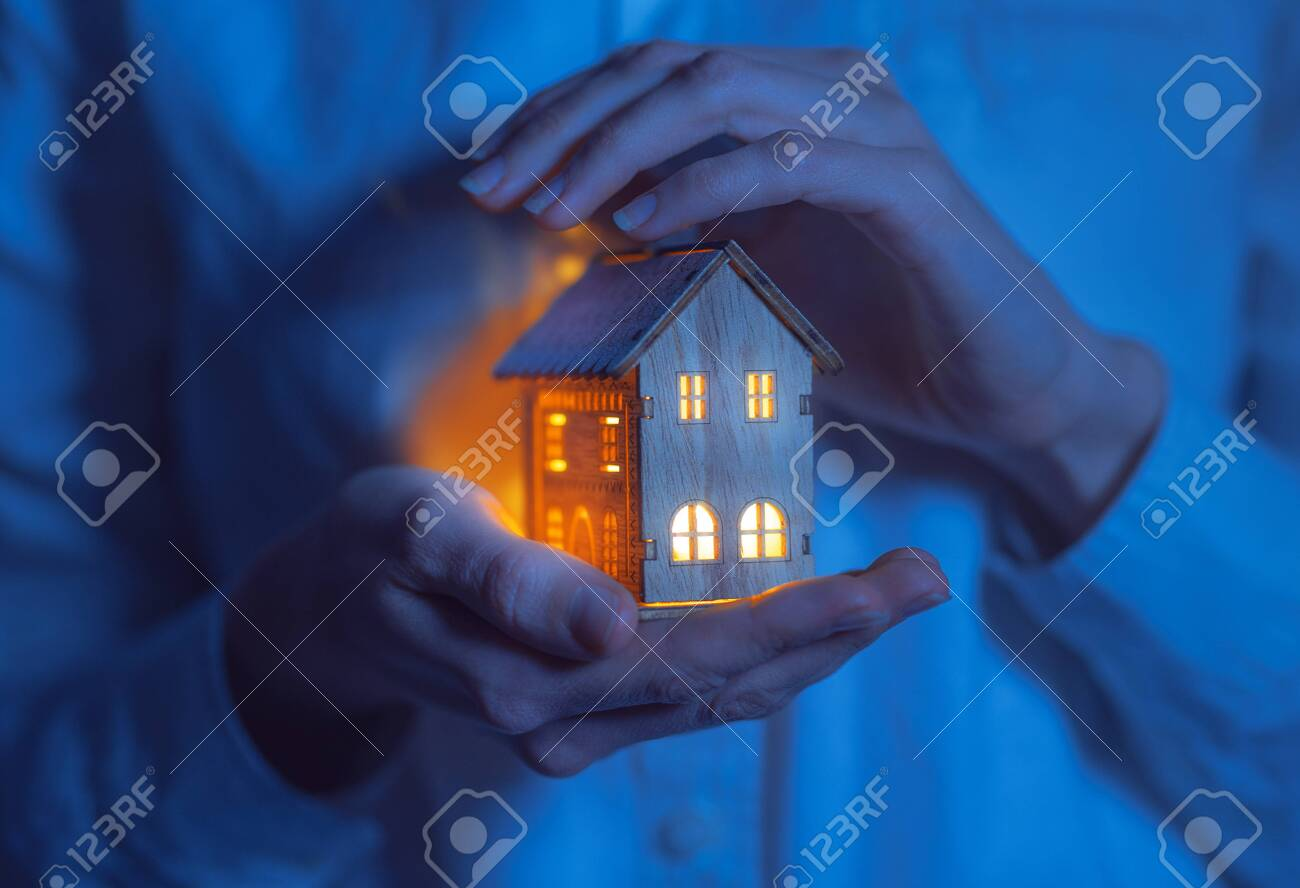 concept technology protection of the house from the cold. house in caring female hands - 134581859