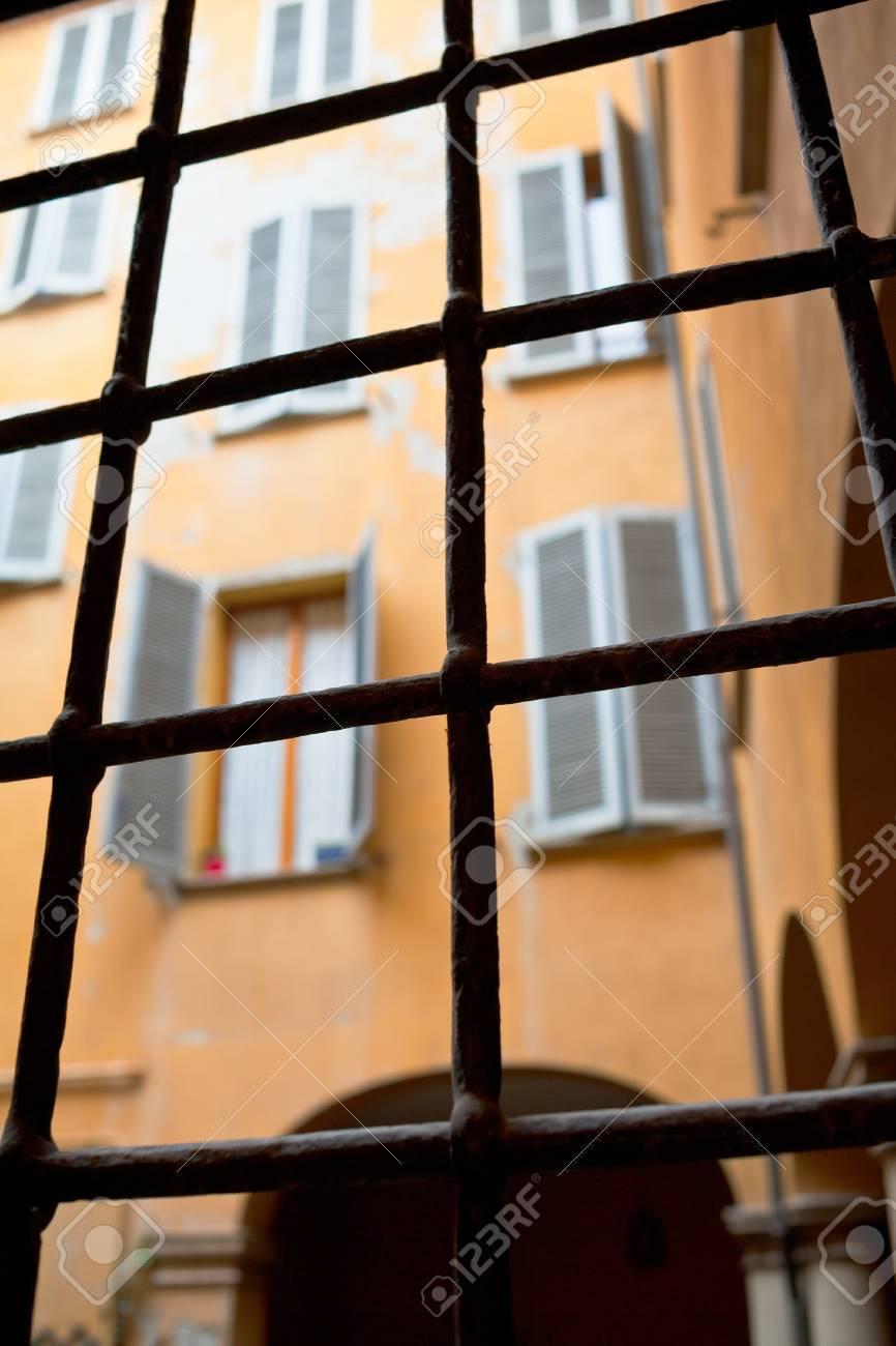 view through window iron bars on italian urban house court Stock Photo - 16862620