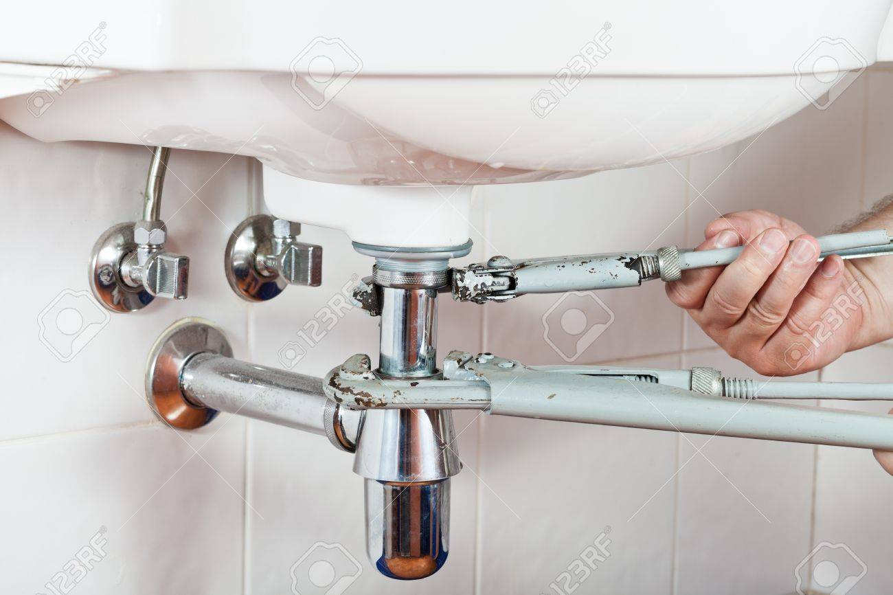 Plumber Repairing Sink Drain By Pipe-wrenches Stock Photo, Picture ...