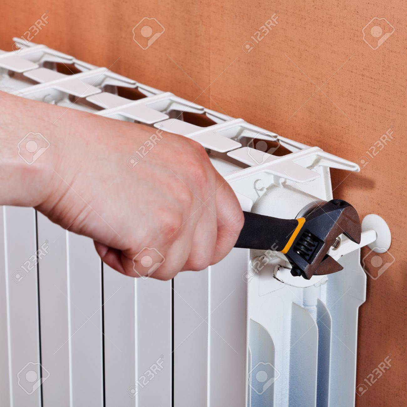 adjusting heating radiator by adjustable wrench Stock Photo - 20632163