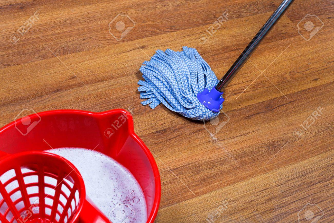 red bucket with water and mopping of laminate floors stock photo