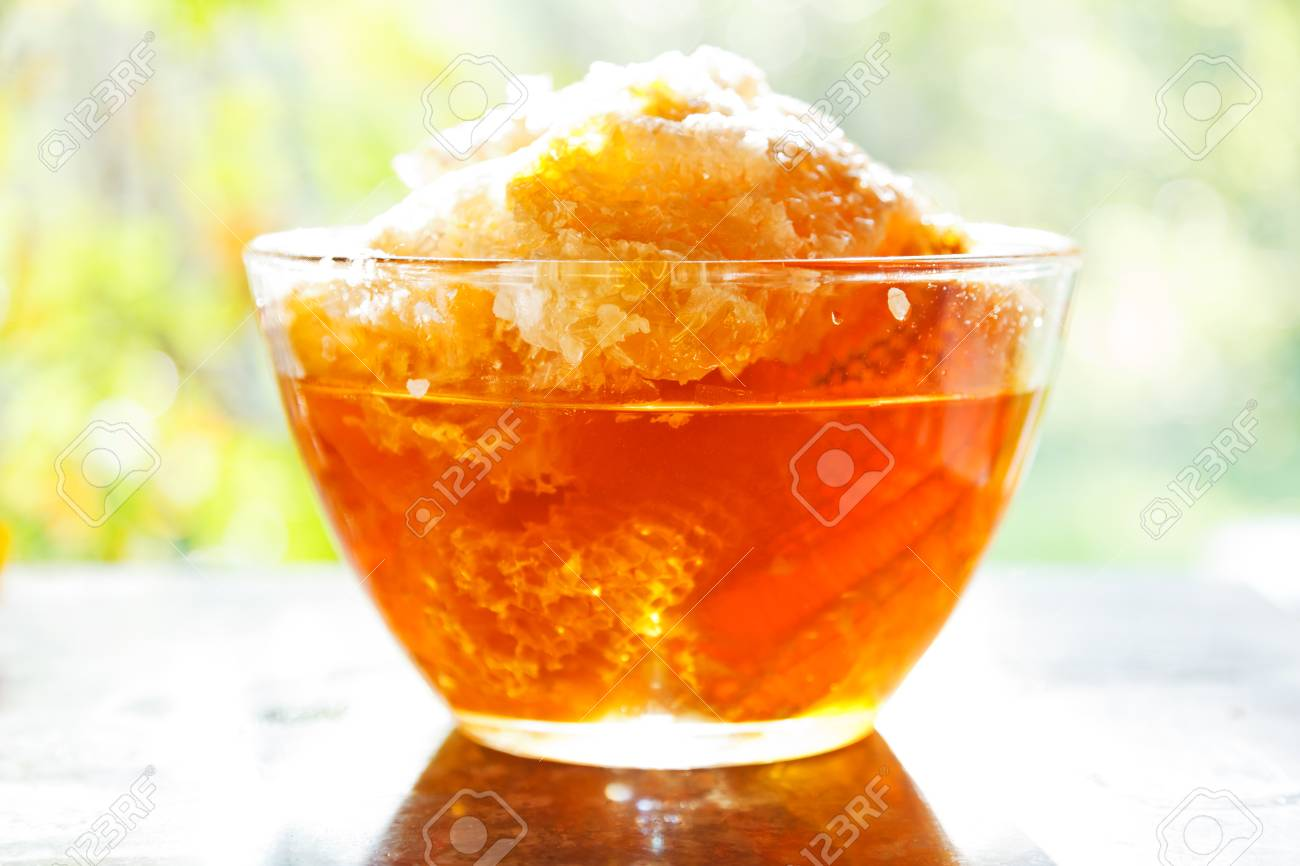fresh honey in comb in glass dish at table with sunshine backlight Stock Photo - 22214782