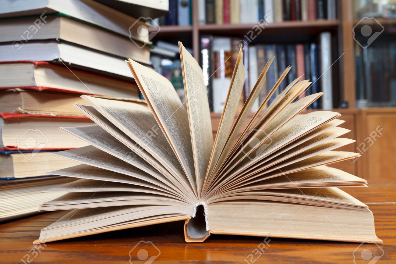 stack of books and fanned open book on wooden table near bookcases Stock Photo - 24613903