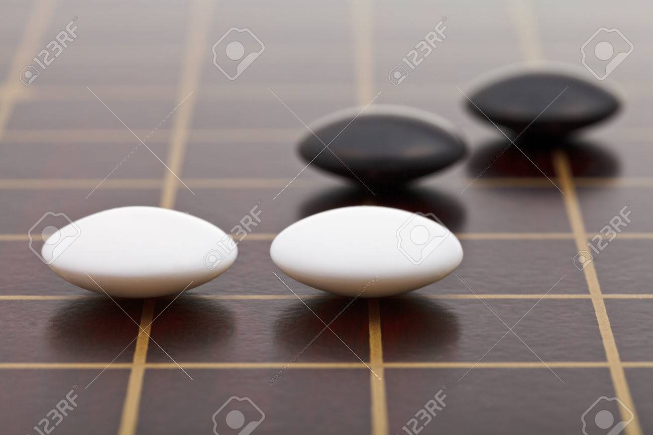 position of few stones during go game playing on wooden board close up - 26863727