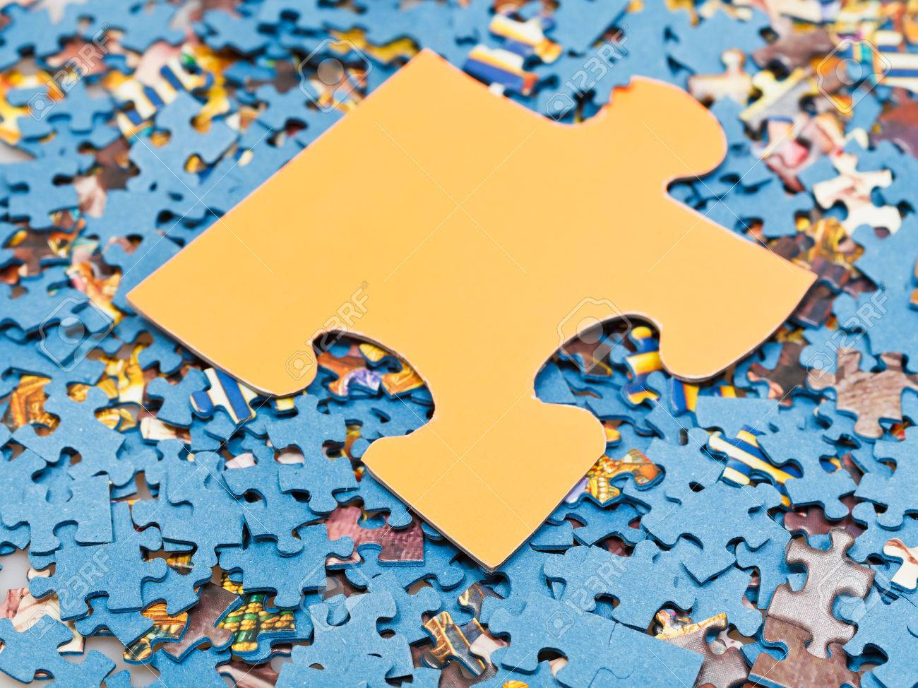 One Big Puzzle Piece On Pile Of Disassembled Little Jigsaw Puzzles Stock Photo