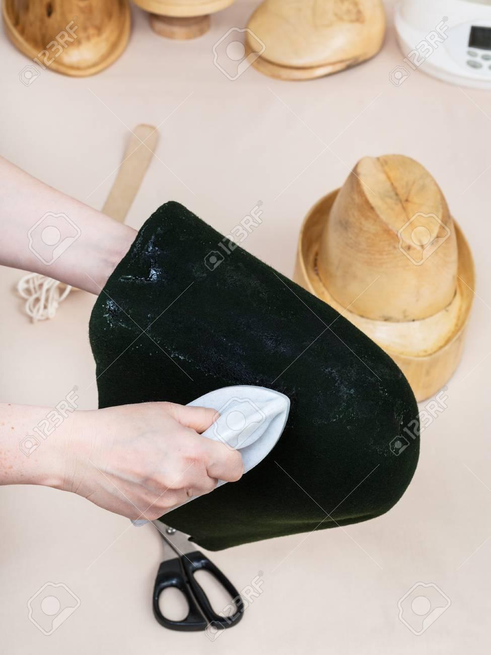 workshop for alpine felt hat making - hatter gluing a felt hood