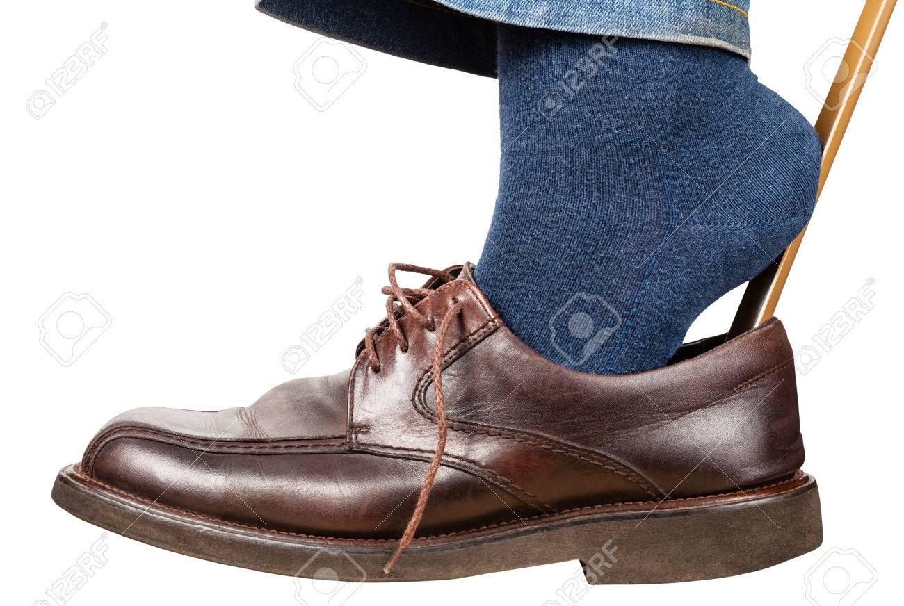 6525ff57c3b Banque d images - Homme met sur les chaussures brunes en utilisant la corne  de chaussure isolé sur fond blanc