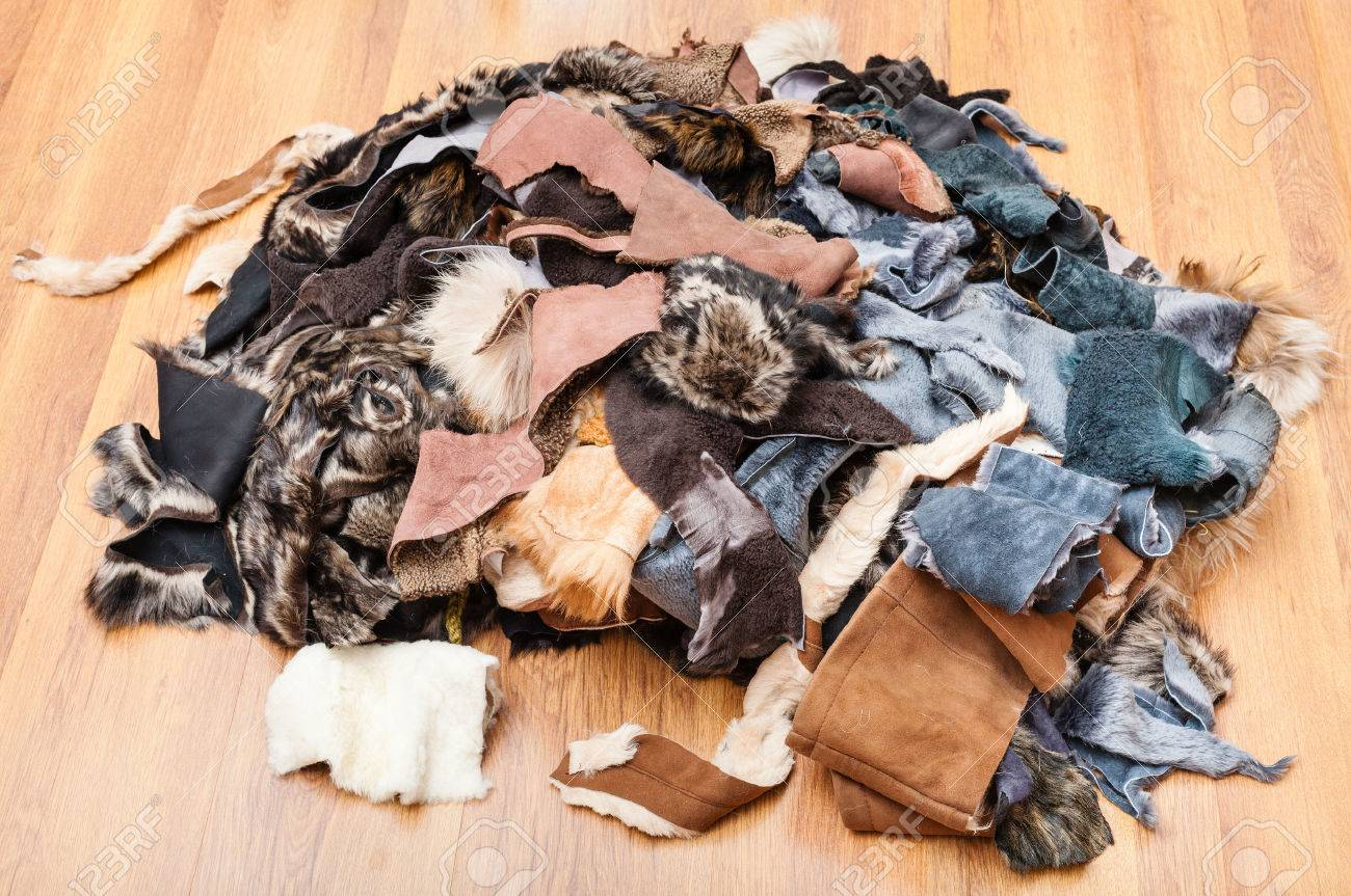 heap of scraps of leather and fur on wooden floor - 54360232