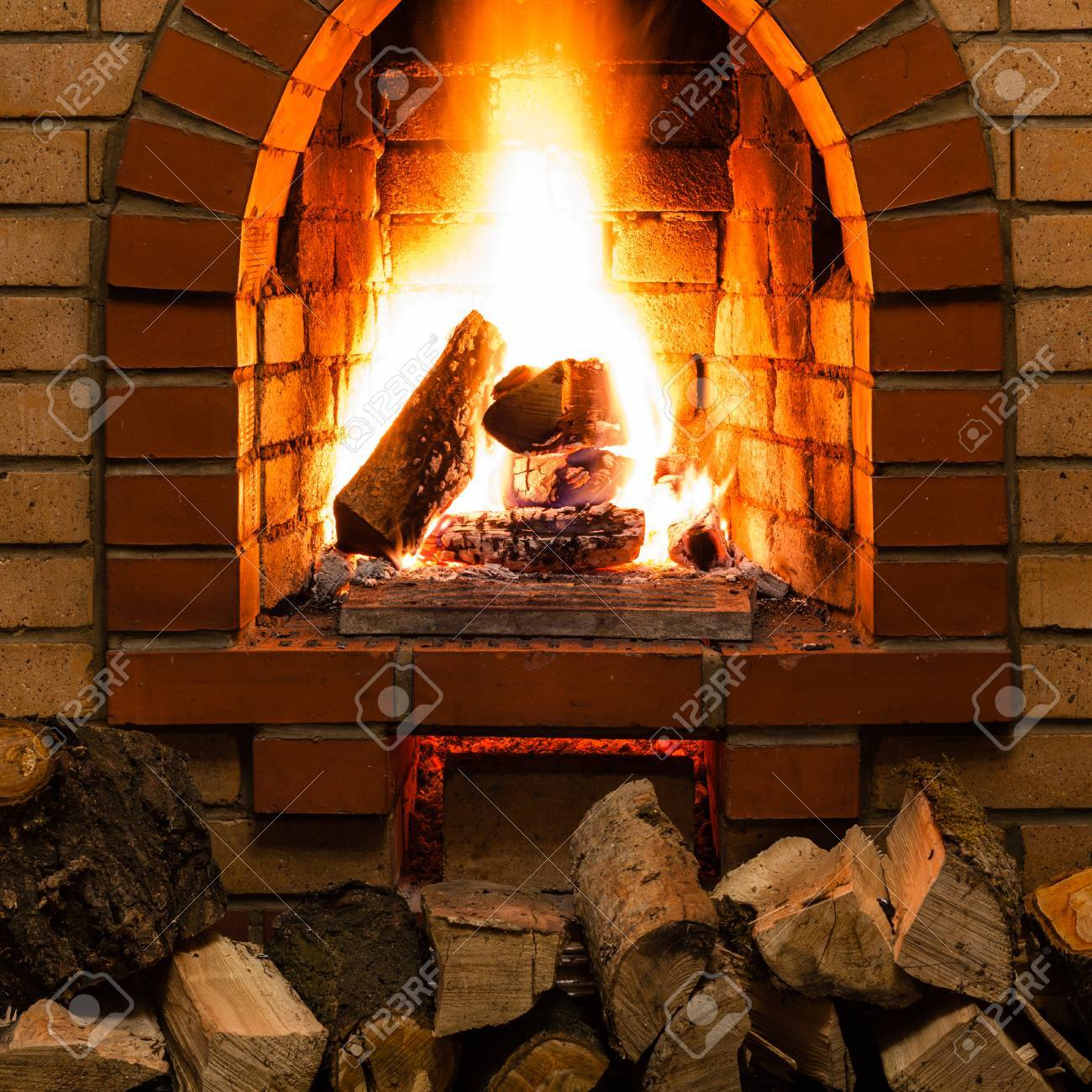 Stack Of Wood And Tongues Of Fire In Indoor Brick Fireplace In