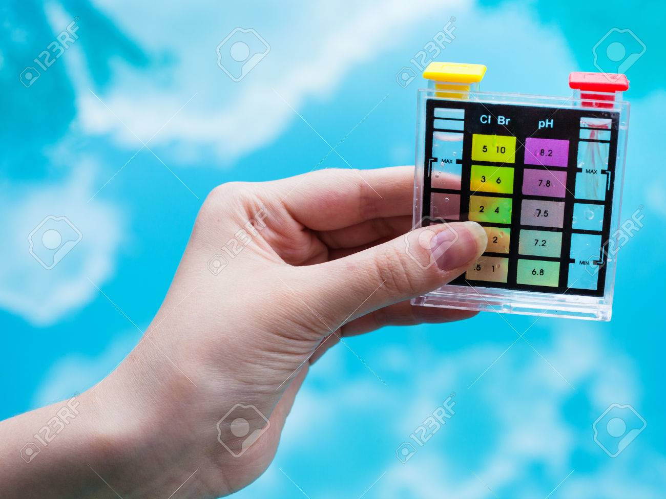 checking pH level in blue outdoor pool by chemical tester - 60883900