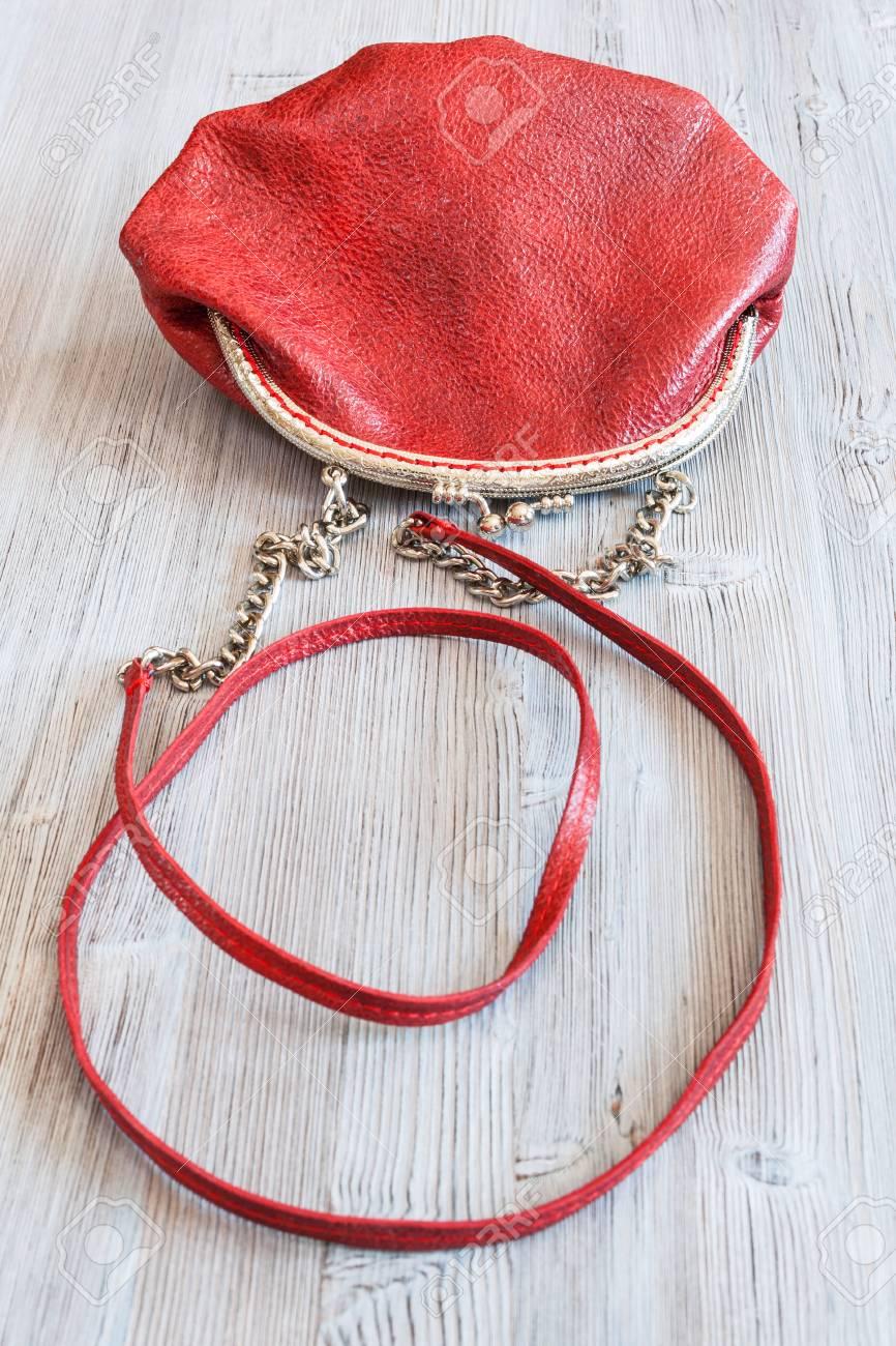 Bolso de cuero rojo de una mujer pequeña sobre tabla de madera