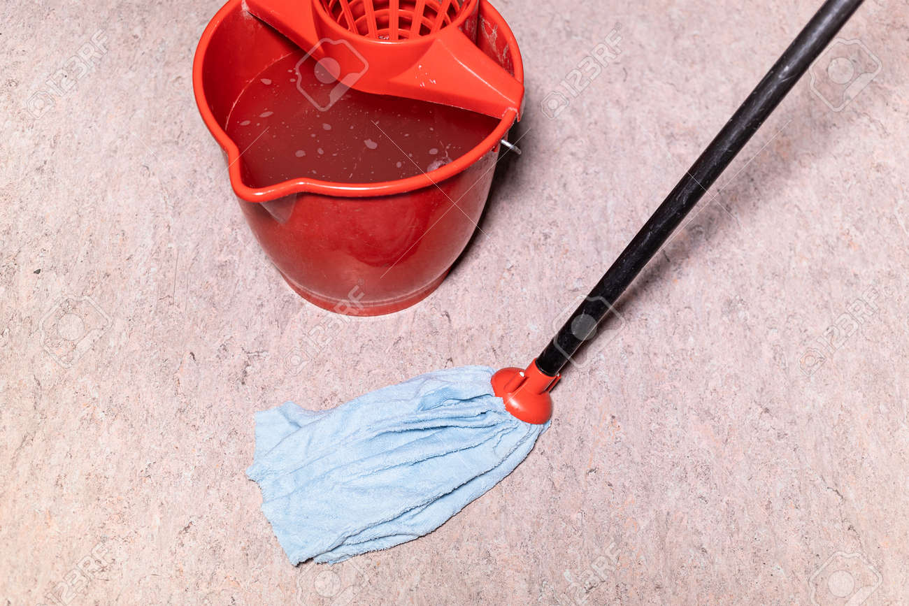 mop cleans linoleum flooring near red bucket with water at home - 163119937